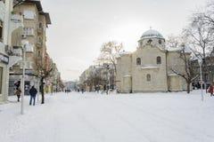 VARNA, BULGARIJE, 28 FEBRUARI, 2018: onbekende persoon die in de sneeuwgang in Varna na sneeuwstorm lopen Het vierkant van Sebast Stock Afbeelding