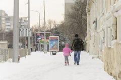 VARNA, BULGARIJE, 28 FEBRUARI, 2018: vader en dochter die onder een sneeuwonweer lopen in Varna Royalty-vrije Stock Foto