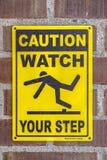 Varna klockan ditt momenttecken på en tegelstenvägg arkivfoto