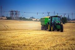 Varna-Region, Bulgarien - 20. Juni 2015: John Deere-Traktor mit dem Anhänger auf Feld Lizenzfreie Stockbilder