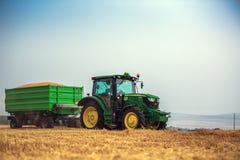 Varna-Region, Bulgarien - 20. Juni 2015: Traktor John Deeres 6115R mit dem Anhänger Lizenzfreie Stockbilder