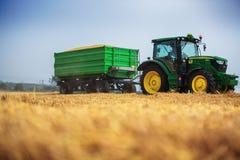 Varna-Region, Bulgarien - 20. Juni 2015: Traktor John Deeres 6115R mit dem Anhänger auf einem gelben Feld Stockfoto