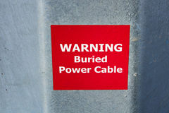 Varnande begravt tecken för maktkabel på metall Pole royaltyfri bild