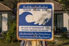 Varnande tecken för tsunami på en strand i sydliga Thailand Anvisningar för thailändskt språk som berättar folk att köra till hög arkivbild