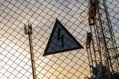 Varnande triangulärt tecken med en blixtbild på det netto staketet Farligt - hög spänning elektrisk avdelningskontor royaltyfria bilder