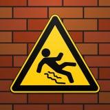 Varning - fara akta sig av halt Säkerhetstecken Det triangulära tecknet på en tegelstenvägg industriell design vektor vektor illustrationer