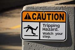 Varning som snubblar faratecknet på en vägg arkivfoto