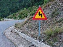Varningstecken för slingrig väg arkivbilder