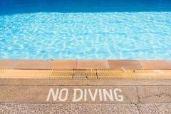 Varningstecken som förbjuder dykning i pölen Royaltyfri Bild