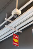 Varningstecken som hänger från CCTV-kamera Arkivbild