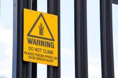Varningstecknet för klättrar inte palissadfäktninggrova spikar kan orsaka allvarlig skada royaltyfria bilder