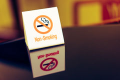 Varningstecknet som förbjuder rök på tabellen Royaltyfri Foto