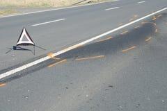 Varningstriangel på grov asfaltbeläggningvägen efter olyckan för bilkrasch Royaltyfri Bild