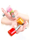 Varnish. A woman holding the vials with different colors varnish Royalty Free Stock Photography