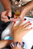 Varnishing nails with red nail and drying Stock Image