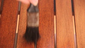 Varnishing Table With Paint Brush. Close up of person painting a wooden table with varnish with a paintbrush by hand stock video footage