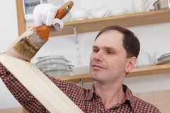 Varnishing wood shelves. Man varnishing wood shelves for kitchen renovation Royalty Free Stock Images