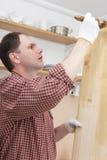 Varnishing wood shelves. Man varnishing wood shelves for kitchen renovation Stock Photo