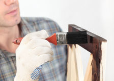 Varnishing a wooden part of furniture. Man varnishing a wooden part of furniture using paintbrush Stock Image