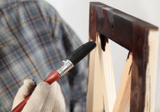 Varnishing a wooden part of furniture Royalty Free Stock Photo