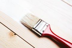 Varnishing a wooden shelf Stock Images