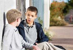 Varones adolescentes jovenes que hablan con el amigo afuera Foto de archivo libre de regalías