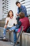 Varones adolescentes y el hablar de la muchacha Foto de archivo libre de regalías