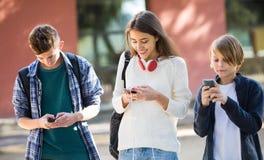 Varones adolescentes y muchacha que entierran con los teléfonos móviles Foto de archivo libre de regalías
