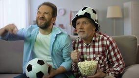 Varones adultos ansiosos que miran el partido de fútbol en la TV, infeliz sobre perder del equipo almacen de video