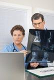 Varredura espinal de leitura do doutor e da enfermeira MRI Fotografia de Stock