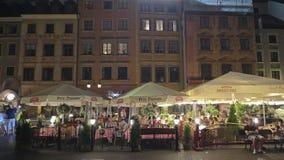 VARSÓVIA, POLÔNIA - 4 DE AGOSTO DE 2018 Restaurante aglomerado da rua na cidade velha na noite fotografia de stock royalty free