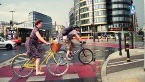 VARSÓVIA, POLÔNIA - 11 DE JULHO DE 2017 Jovem mulher que monta sua bicicleta clássica na cidade Tráfego urbano moderno da rua foto de stock royalty free