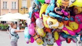 VARSÓVIA, POLÔNIA - 10 DE JUNHO DE 2017 O vendedor ambulante fêmea vende balões múltiplos do hélio do personagem de banda desenha Imagem de Stock