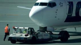 VARSÓVIA, POLÔNIA - MAIO, 18, 2017 O caminhão de reboque do aeroporto reboca o avião de passageiros Tiro da lente teleobjetiva Foto de Stock Royalty Free
