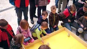 VARSÓVIA, POLÔNIA - MARÇO, 4, 2017 Crianças que operam entusiasticamente robôs pequenos do giroscópio usando o tablet pc Imagens de Stock Royalty Free