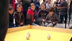 VARSÓVIA, POLÔNIA - MARÇO, 4, 2017 Crianças que operam robôs pequenos Sphero do giroscópio usando o PC da tabuleta Imagens de Stock