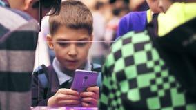 VARSÓVIA, POLÔNIA - MARÇO, 4, 2017 Menino que está na multidão e que guarda o telefone celular roxo tiro do close-up 4K filme
