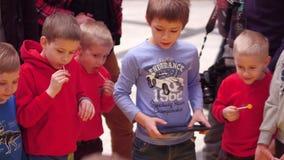 VARSÓVIA, POLÔNIA - MARÇO, 4, 2017 Rapazes pequenos que operam entusiasticamente robôs pequenos usando o tablet pc Imagens de Stock