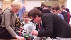 VARSÓVIA, POLÔNIA - MARÇO, 4, 2017 Robô pequeno e família de DIY que apoiam o participante novo da competição da robótica imagens de stock royalty free