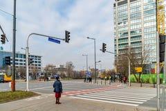 Varsavia Polonia 18 febbraio 2019 La donna anziana sta davanti ad un passaggio pedonale Ad un semaforo i tre colori fotografia stock libera da diritti