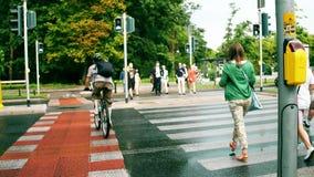 VARSAVIA, POLONIA - 11 LUGLIO 2017 I pedoni ed i ciclisti attraversano la via della città all'attraversamento Fotografia Stock Libera da Diritti