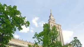 Varsovia Polonia Casa de la cultura y de la ciencia El movimiento de la c?mara, visi?n a trav?s de los ?rboles verdes almacen de metraje de vídeo