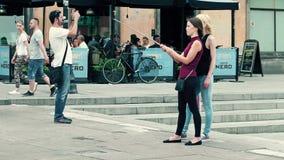 VARSOVIA, POLONIA - 10 DE JUNIO DE 2017 Las mujeres jovenes hacen selfies en un lugar turístico, ciudad vieja Fotos de archivo libres de regalías