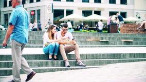 VARSOVIA, POLONIA - 10 DE JUNIO DE 2017 Los pares jovenes se sientan en la calle y utilizan sus teléfonos móviles Imagen de archivo