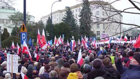 VARSOVIA, POLONIA - DICIEMBRE, 17, 2016 Manifestantes con el polaco y banderas de la UE en la calle tiro de arriba de la cacerola almacen de video