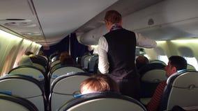 VARSOVIA, POLONIA - DICIEMBRE, 24 SORTEE al asistente de vuelo de sexo femenino en los pasajeros del trabajo y del avión de pasaj almacen de metraje de vídeo