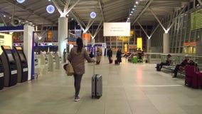 VARSOVIA, POLONIA - DICIEMBRE, 24 tiros de Steadicam de pasajero femenino en el área del enregistramiento del terminal de aeropue metrajes