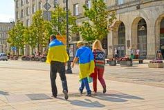 Varsovia, Polonia La gente joven que se envuelve para arriba en las banderas ucranianas va abajo de la calle Fotos de archivo