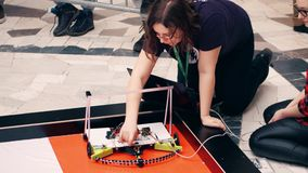 VARSOVIA, POLONIA - MARZO, 4, 2017 Robot de DIY y participante femenino joven de la competencia de la robótica foto de archivo