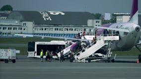 VARSOVIA, POLONIA - MAYO, 18, 2017 Embarque del avión de pasajeros de Wizz Air Airbus A320-232 vía dos rampas en el aeropuerto HD Imagen de archivo libre de regalías
